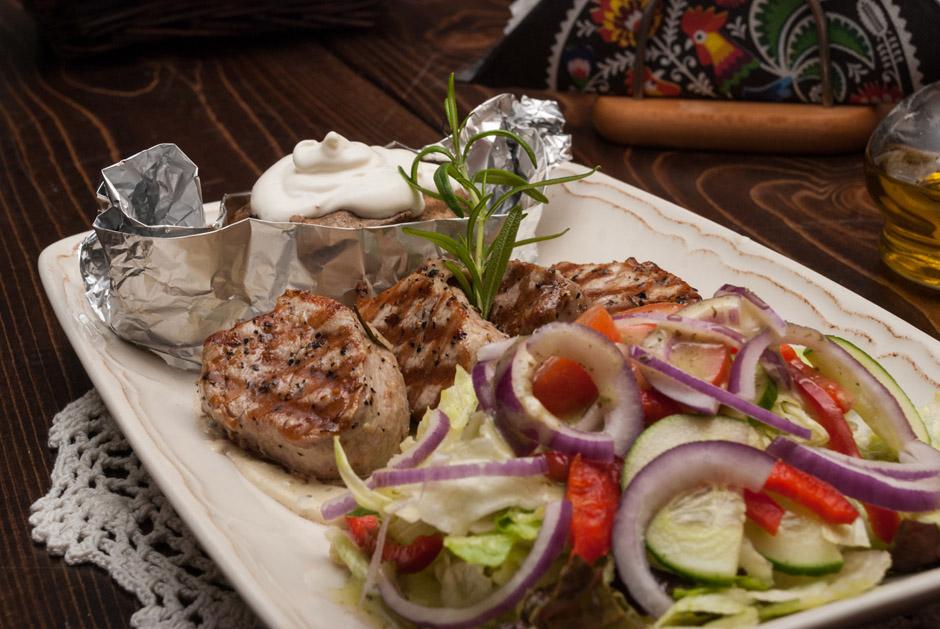 Pieprzne Polędwiczki podane z pieczonym ziemniakiem, lekko czosnkowym sosem. Podobnie jak w innych daniach, porcja jest duża i sycąca.